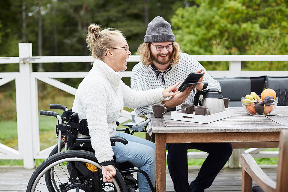 woman in wheelchair and man looking at a tablet